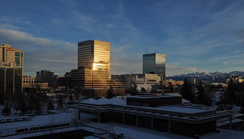 Sunrise reflected from oil buildings, Chugach mountain range in background, Anchorage, Alaska