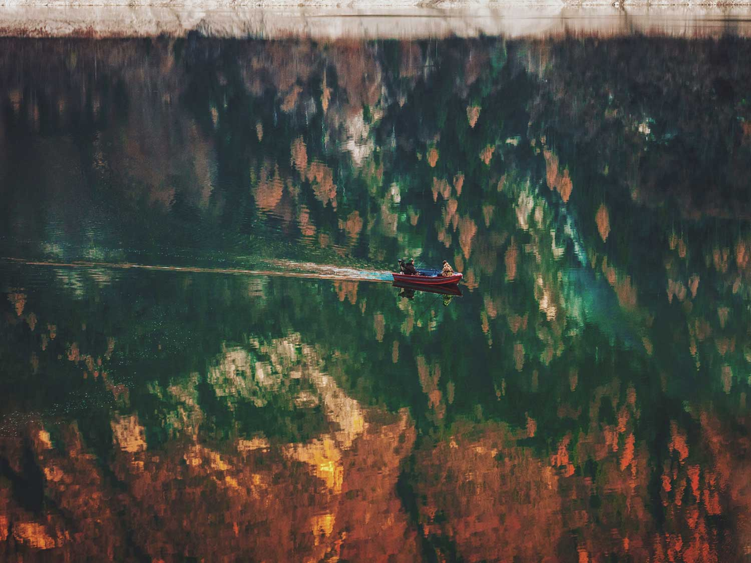 Boat on a river in Italy with autumn reflections